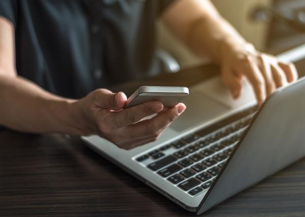 Junger Mann recherchiert im Internet und hält ein Smartphone in der Hand